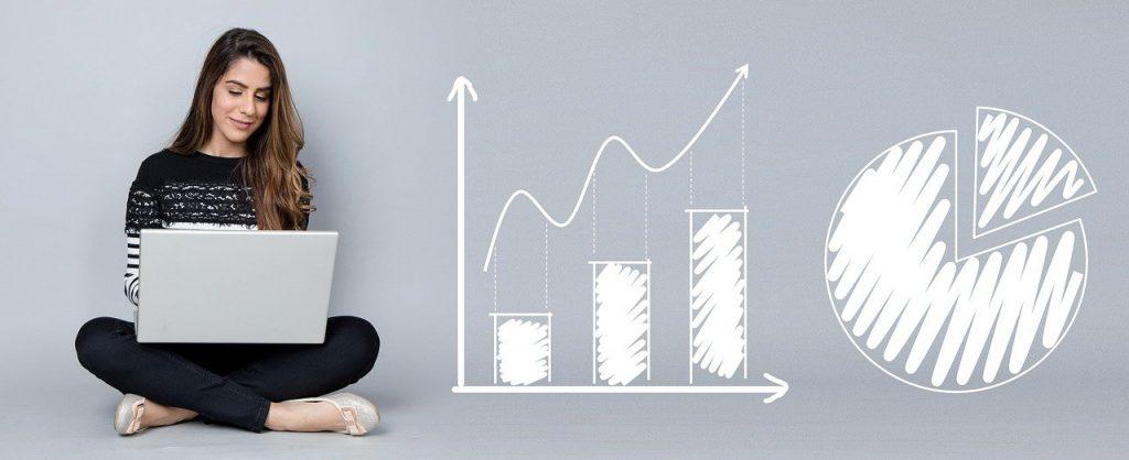 Kobieta przy komputerze i wykresy liczbowe - wzrosty finansowe